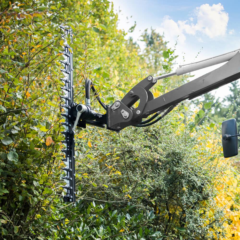 A hedge trimmer cuts a hedge