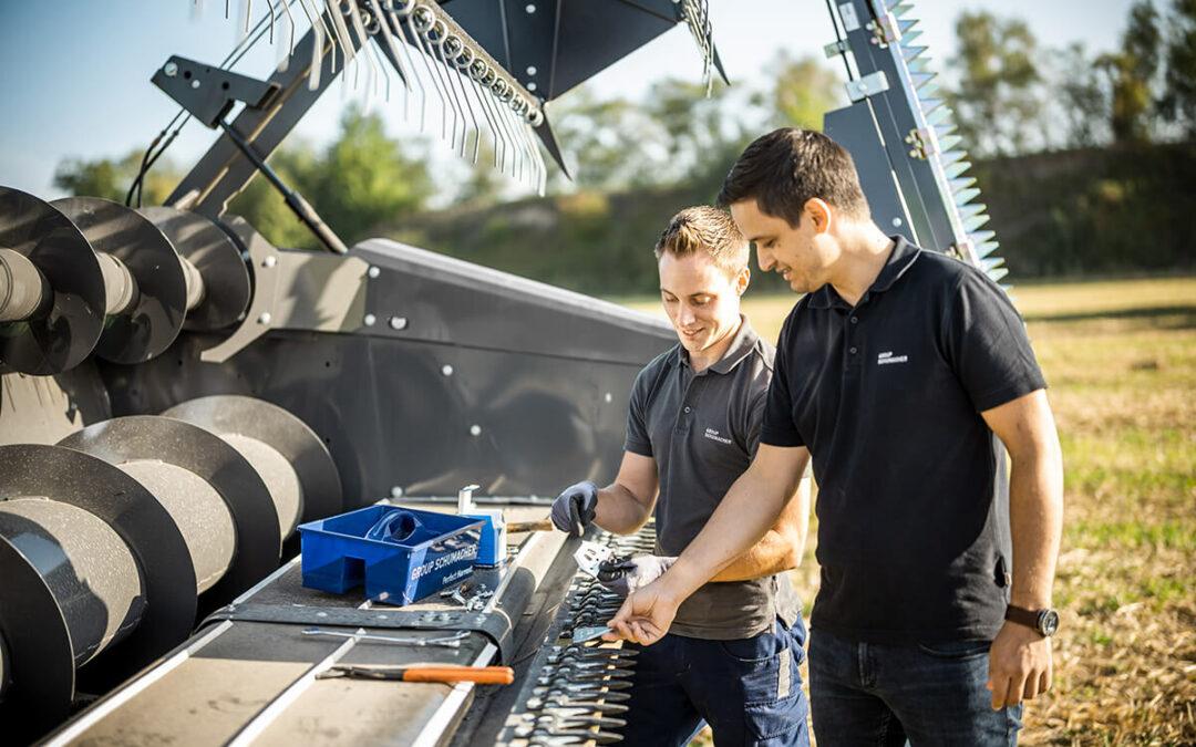 Zwei Männer arbeiten zusammen am Mähdrescher
